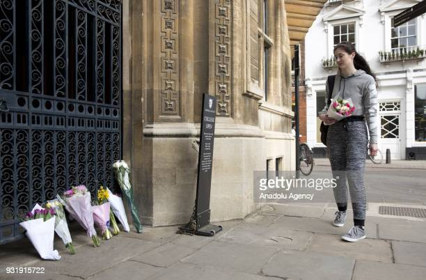 A girl brings flowers to the gate of Gonville and Caius College in Cambridge United Kingdom to pay tribute to world renowned physicist Stephen...