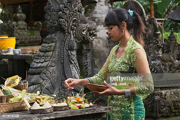 a girl brings offerings to the pura tirta empul temple complex during the galungan festival - tampaksiring, bali, indonesia - pura tirta empul temple stock pictures, royalty-free photos & images