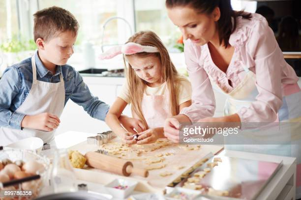 girl, brother and mother baking easter biscuits at kitchen counter - happy easter mom stock pictures, royalty-free photos & images