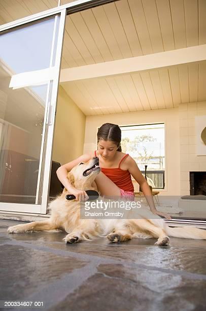 Girl (9-11) brushing dog on patio