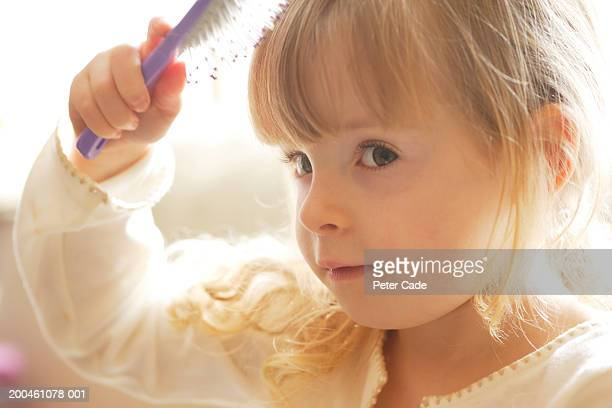 Girl (3-5) brushing hair, close-up