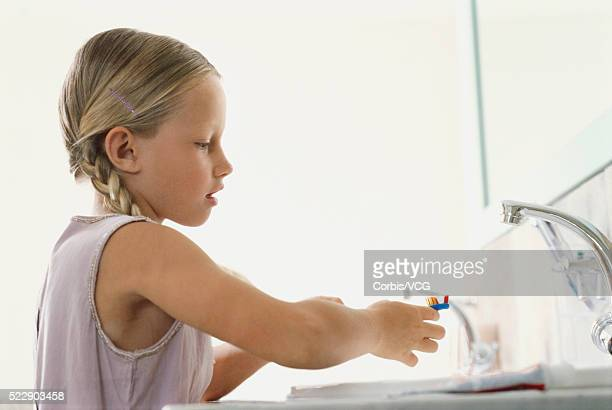 Girl Brushing Her Teeth at the Sink