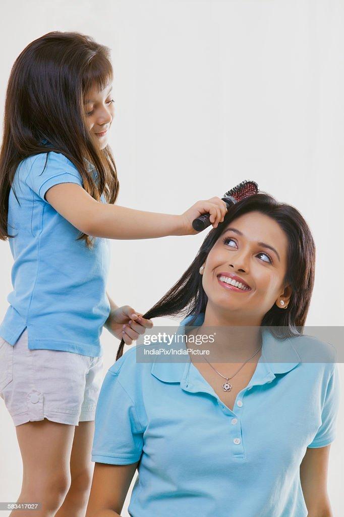 Girl brushing mothers hair : Stock Photo