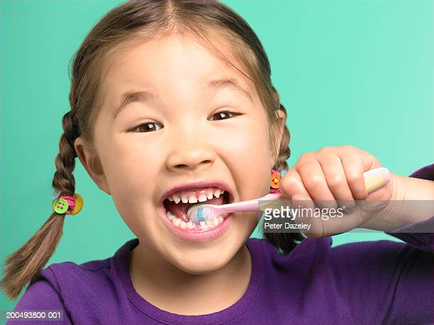 Girl (5-7) brushing teeth, one tooth missing, close-up, portrait