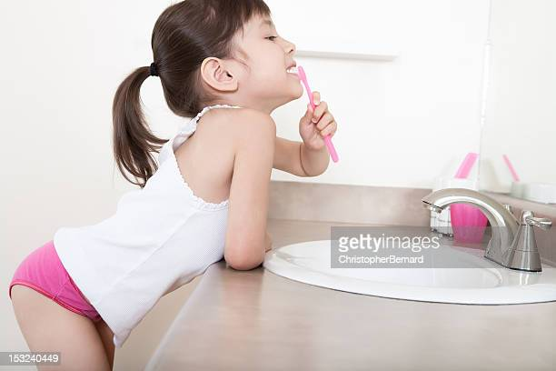 girl brushing teeth - pants stock photos and pictures