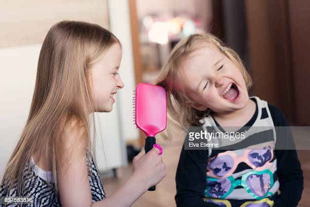 Girl brushing younger girl's tangled hair