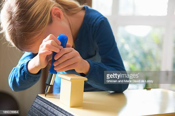 Girl building a doll house, using screwdriver