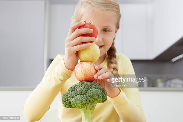 Girl building tower of apples and broccoli