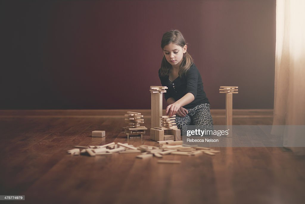 girl building with wooden blocks : Stock Photo
