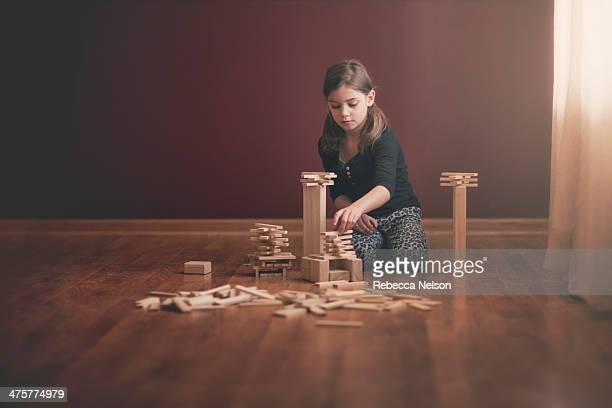 girl building with wooden blocks