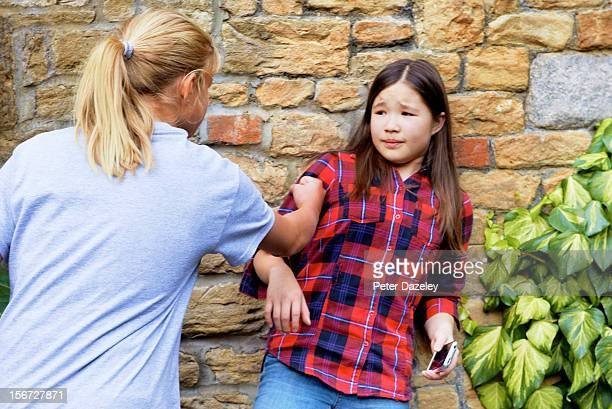 a girl bullying another for her mobile phone - girl fight stock photos and pictures