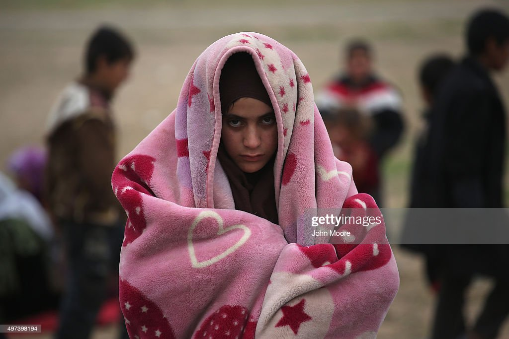 A girl bundles against the cold while fleeing an ISIL or Daesh-held frontline village on November 16, 2015 to Sinjar, Iraq. Peshmerga forces carefully screened the displaced Iraqis as they arrived, fearing enemy infiltrators and suicide bombers. Kurdish forces, with the aid of massive U.S.-led coalition airstrikes, liberated Sinjar from ISIL extremists, known in Arabic as Daesh, moving the frontline south. About a thousand villagers in Ghabosyeh fled north to Kurdish held territory, to take refuge camps or onward as refugees to Turkey or Europe.