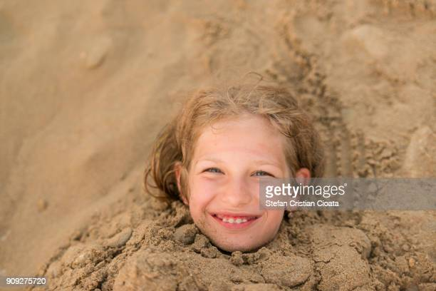 Girl Buried in sand up to her neck