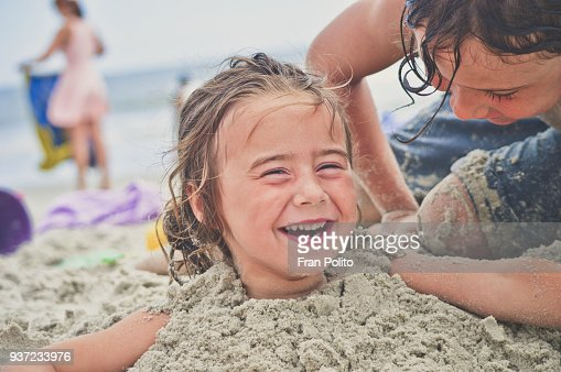 Girl buried in the sand at the beach.