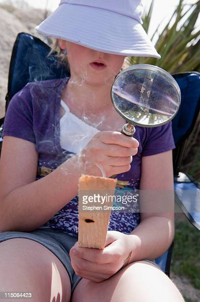 girl burning wood with a magnifying glass