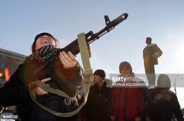 A girl bursts into laughter as she holds a Kalashnikov submachine gun during a rally devoted to the national holiday celebration the Day of the...