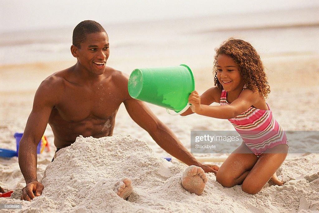 Girl burying dad in sand : Stock Photo