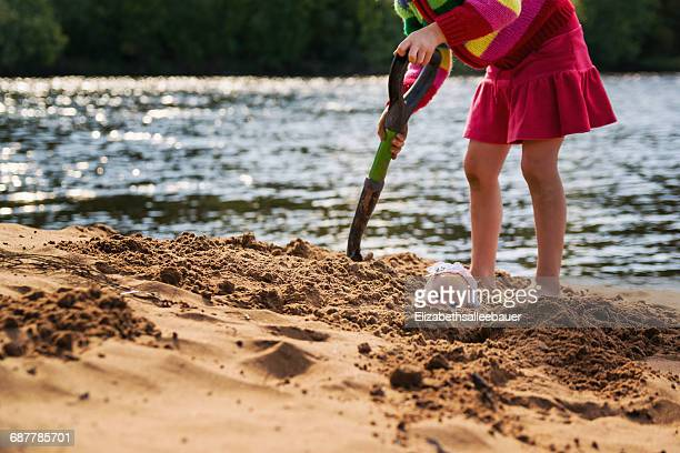 girl burying her doll in the sand - burying stock pictures, royalty-free photos & images