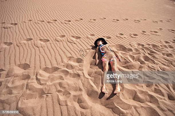 girl burying self in sand - great sand dunes national park stock pictures, royalty-free photos & images