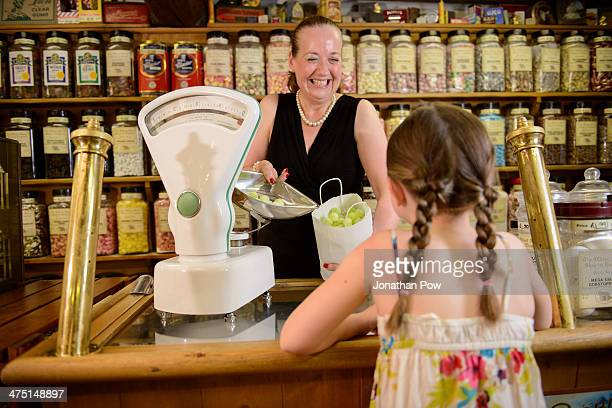 girl buying bag of sweets from traditional sweet shop - sweet shop stock pictures, royalty-free photos & images