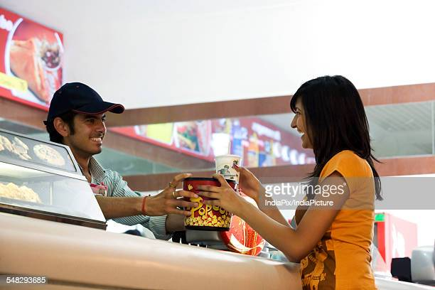 Girl buying popcorn and cola