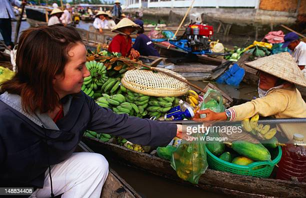 Girl buying some bananas at a floating market.