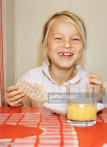 A girl by a breakfast table.