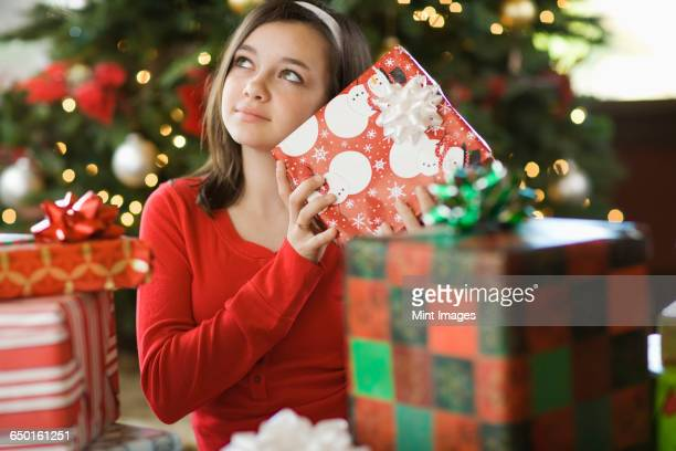 A girl by a Christmas tree shaking a present trying to guess what it is.