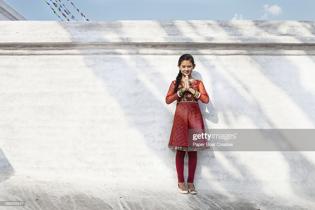 Girl by a white wall doing Namaste hand gesture : Stock Photo