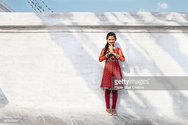 girl by a white wall doing namaste hand gesture - prayer pose greeting bildbanksfoton och bilder