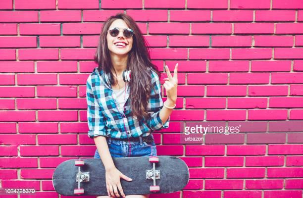 mädchen mit rosa ziegelwand mit skateboard - friedenszeichen handzeichen stock-fotos und bilder