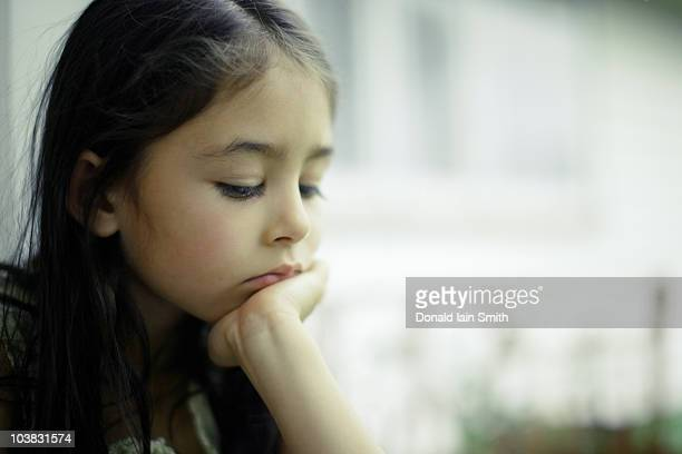 girl by window with chin resting on hand - hand on chin stock pictures, royalty-free photos & images