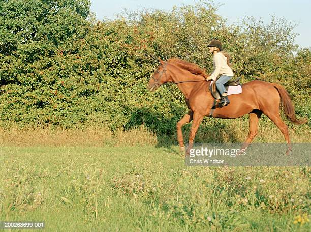 Girl (10-12) cantering through field, side view (blurred motion)