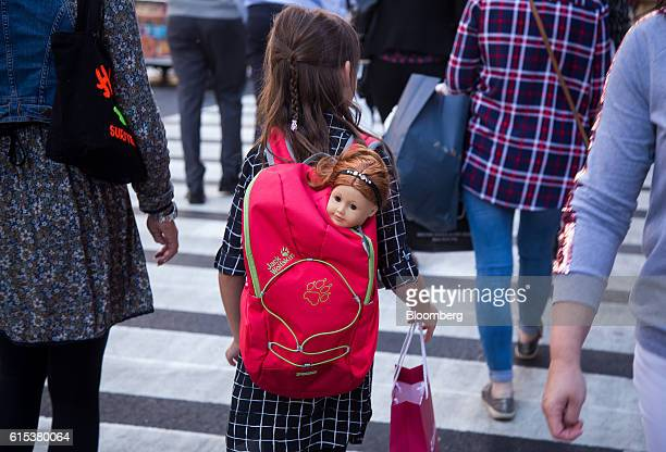 A girl carries an American Girl doll in a backpack while walking along 5th Avenue in New York US on Monday Oct 17 2016 Mattel Inc the parent company...