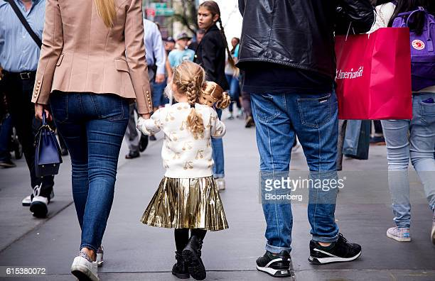 A girl carries an American Girl doll while walking along 5th Avenue in New York US on Monday Oct 17 2016 Mattel Inc the parent company of American...