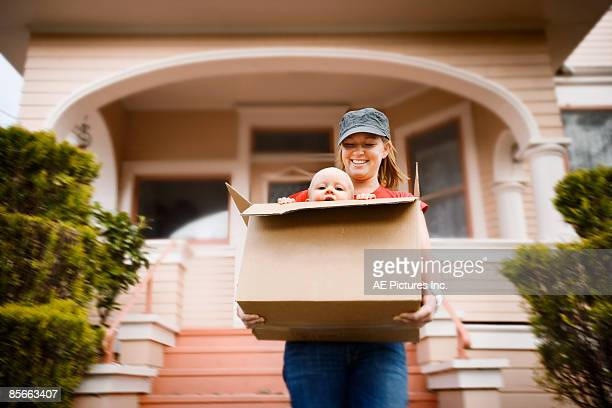 Girl carries baby in moving box