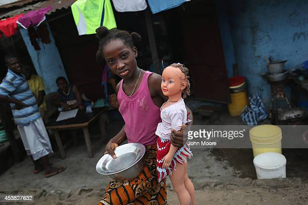 A girl carries her doll on August 19 2014 in Monrovia Liberia A holding center in West Point for people suspected of having the Ebola virus was...