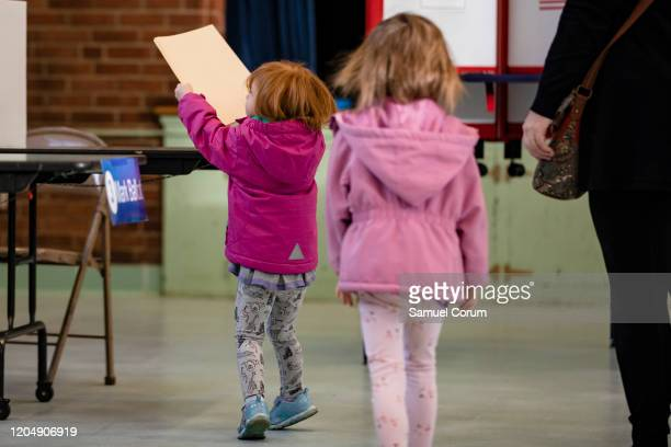 A girl carries her mothers ballot to the table where she will fill in her choice in the Democratic presidential primary elections at the Taylor...