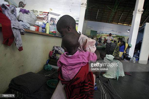 A girl carries her sister in their new shelter at the Jamhuri grounds in Nairobi 02 January 2008 where they have spent three days after fleeing their...