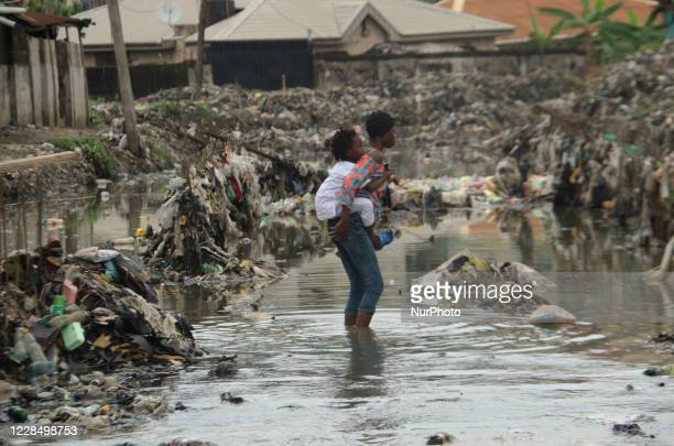 Girl carries her young brother on her back as they walk through a flooded cannal, following rain fall at Oyebanjo Solarin Street in Ketu, Lagos which...