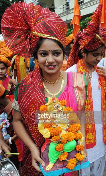 A girl carries Lord Ganesha idol in a procession before the idol immersion on the occasion of Anant Chaturdashi on September 15 2016 in Bhopal India