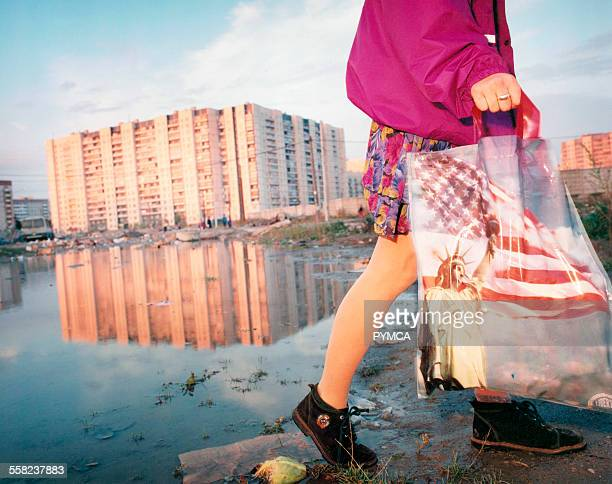 Girl carries shopping bag with Statue of liberty on it through flooded wasteland St Petersburg