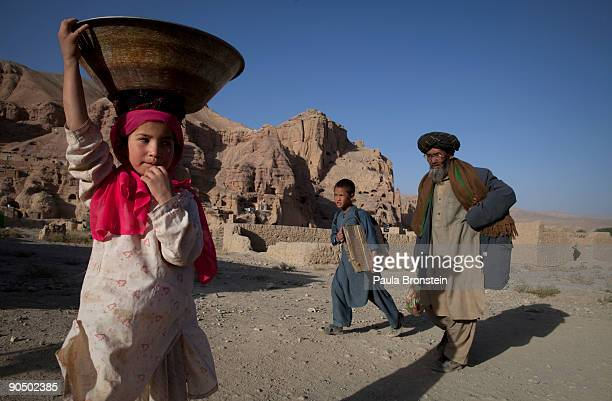 A girl carries some washed clothing as Afghans living in the caves head home September 2 2009 in Bamiyan Afghanistan Many of the impoverished...