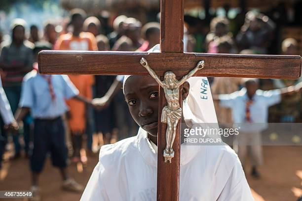 A girl carrying a cross arrives to celebrate mass at Saint Charles Lwanga church in Bangui on December 15 2013 The Central African Republic's...
