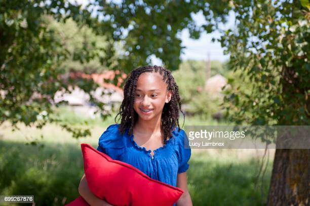 Girl carrying a cushion for a picnic