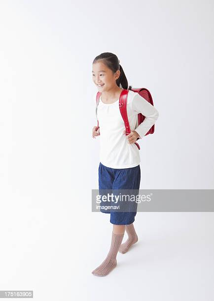 Girl carrying a school bag on shoulders