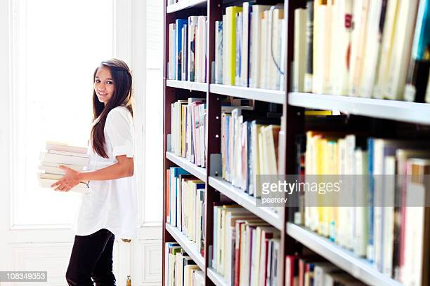 girl carrying books in library