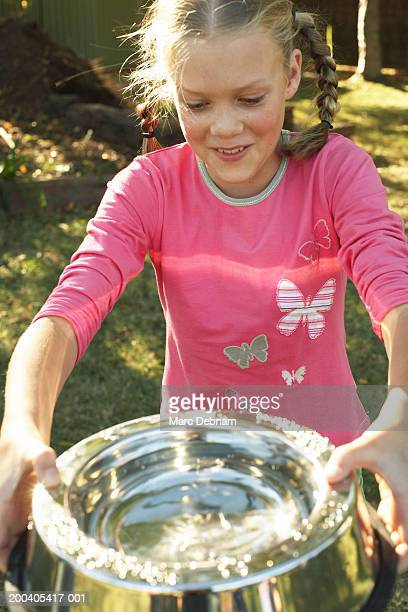 Girl (10-12) carrying bowl full of water, smiling, close-up