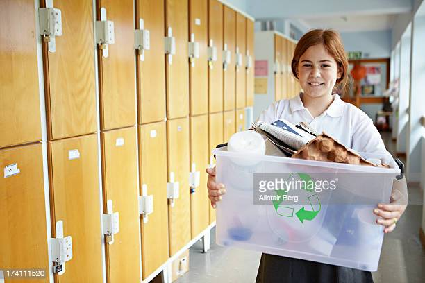 Girl carrying box of recycling