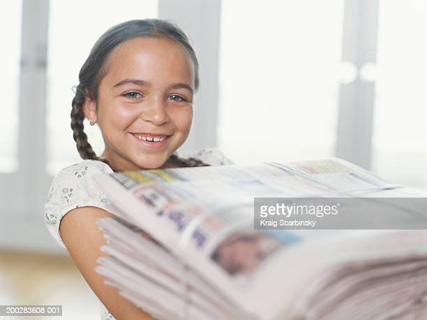 girl (6-8) carrying bundle of newspapers, smiling, portrait - carrying stock pictures, royalty-free photos & images